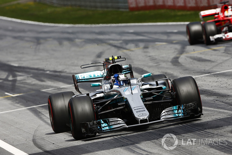 Valtteri Bottas, Mercedes AMG F1 W08, lifts his arm in victory celebration at the finish, ahead of Sebastian Vettel, Ferrari SF70H