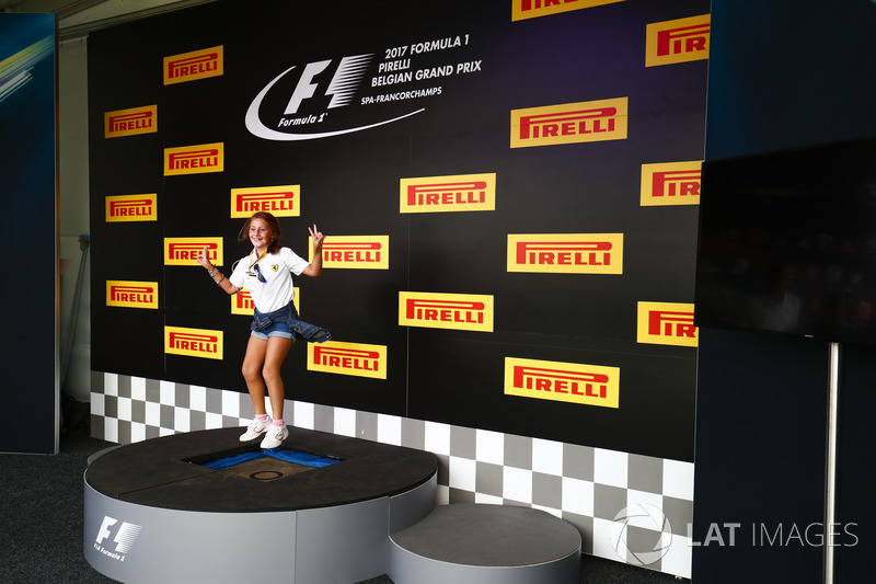 A fan tries the podium out in the F1 Fanzone