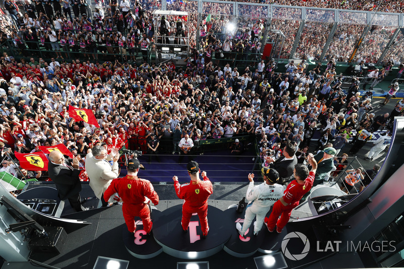 Sebastian Vettel, Ferrari, celebrates victory on the podium with Lewis Hamilton, Mercedes AMG F1, and Kimi Raikkonen, Ferrari