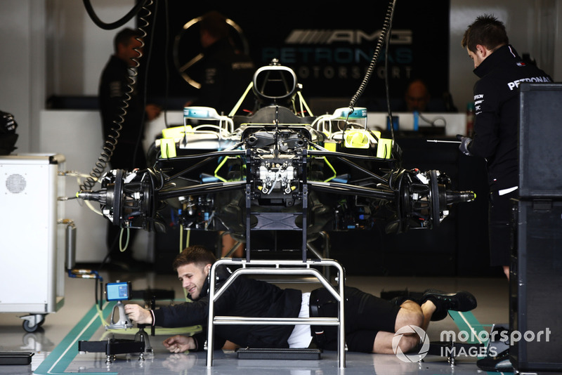 Mechanics work on a Mercedes AMG F1 W09 EQ Power + in the garage.