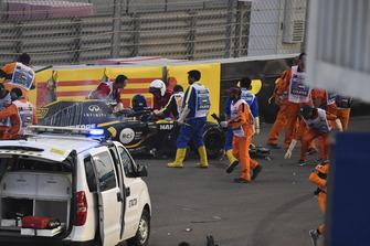Медики и маршалы помогают пилоту Renault Sport F1 Team Нико Хюлькенбергу выбраться из опрокинутого в аварии автомобиля RS18