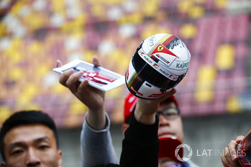 Fans wave items for Sebastian Vettel, Ferrari, to autograph
