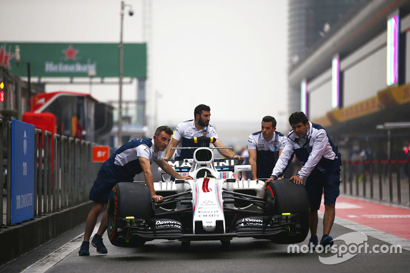 Williams team members push a Williams FW40