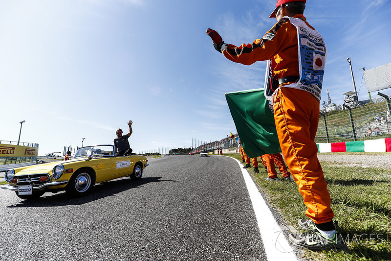 Marshals line the track as Fernando Alonso, McLaren, passes in the drivers parade