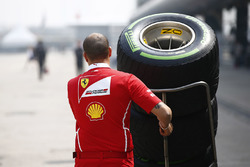 A Ferrari team members pushes a stack of Pirelli tyres