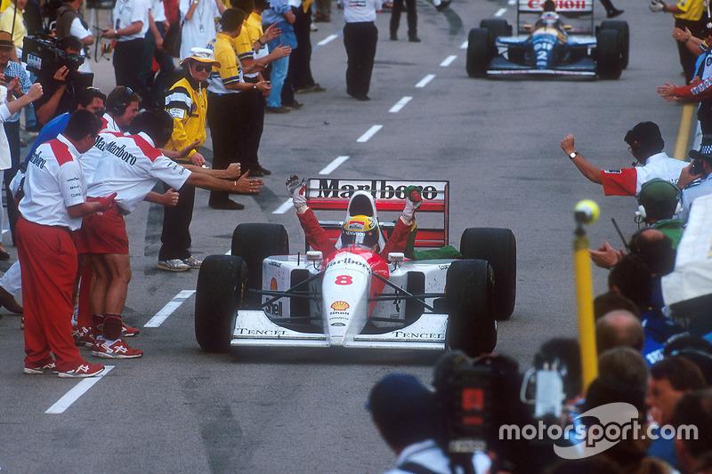Ayrton Senna, McLaren fête sa victoire dans la ligne des stands vers le parc fermé
