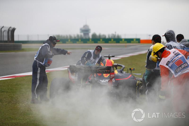 Des commissaires prennent en charge la voiture de Daniel Ricciardo Red Bull Racing RB14 Tag Heuer, après sa défaillance moteur