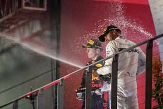 Max Verstappen, Red Bull Racing, 2nd position, and Lewis Hamilton, Mercedes AMG F1, 1st position, spray Champagne on the podium