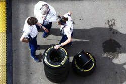 Rob Smedley, Head of Vehicle Performance, Williams, and colleagues hold a discussion next to a stack of Pirelli wheels