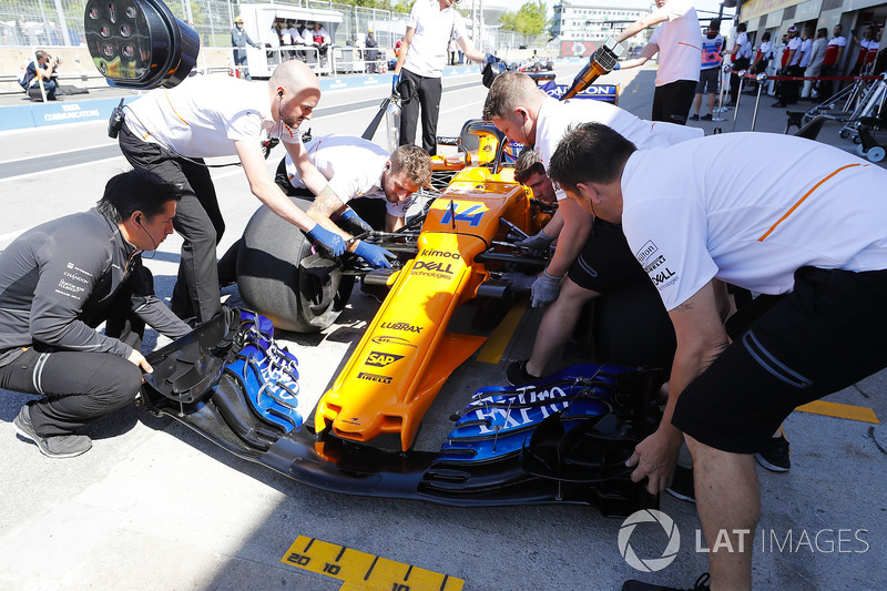 Mechanics work on the Fernando Alonso McLaren MCL33 in the pit lane
