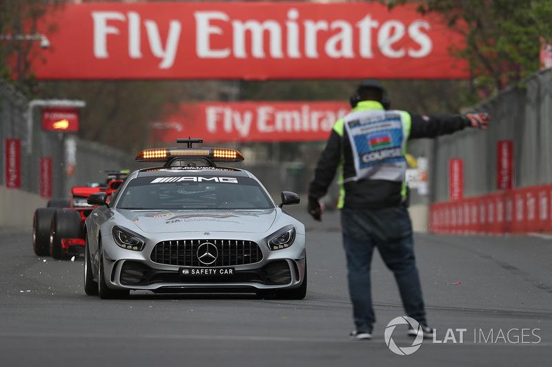 Safety car dan marshal mengarahkan pembalap