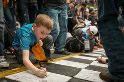 Fans sign the Start-finish-line
