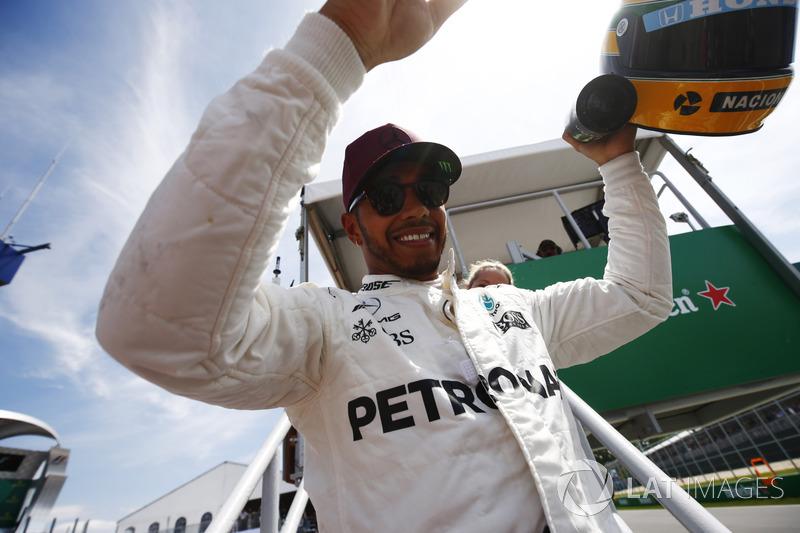 Гонщик Mercedes AMG F1 Льюис Хэмилтон показывает болельщикам подаренный ему шлем Айртона Сенны