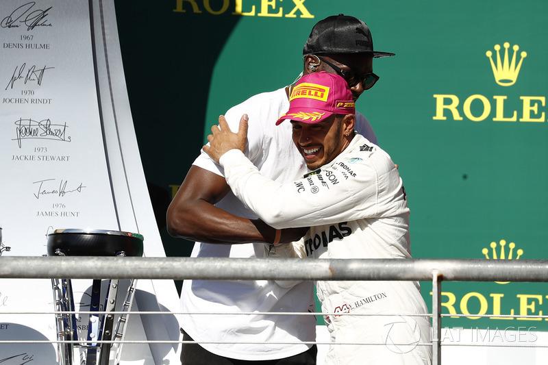 El abrazo entre el ganador de la carrera, Hamilton, Mercedes AMG F1, con Usain Bolt en el podio