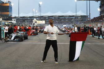 Will Smith waves the flag of the United Arab Emirates at the start of the race.