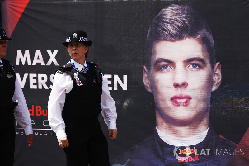 A Police Officer walks past a portrait of Max Verstappen, Red Bull