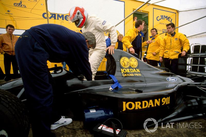 Джон Вотсон піднімається на борт нового Jordan 911 Форд, поки дизайнер Гері Андерсон і Енді Стівенсон спостерігають