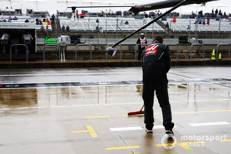 Un meccanico Haas F1 asciuga la piazzola box con una scopa