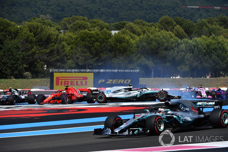 Lewis Hamilton, Mercedes-AMG F1 W09 lidera al inicio de la carrera mientras Sebastian Vettel, Ferrari SF71H golpea a Valtteri Bottas, Mercedes-AMG F1 W09