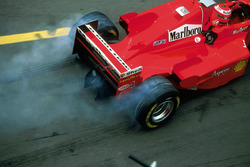 Eddie Irvine, Ferrari F300 smokes his tyres as he leaves the pits after his pitstop