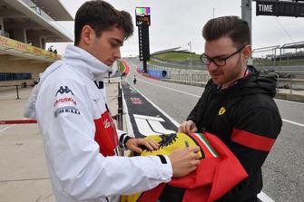 Charles Leclerc, Alfa Romeo Sauber F1 Team signs an autograph on a Ferrari flag