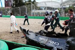 Fernando Alonso bekijkt zijn McLaren MP4-31 na crash