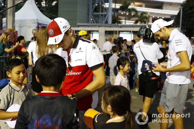 Charles Leclerc, Sauber, and Esteban Ocon, Racing Point Force India, sign autographs for grid kids