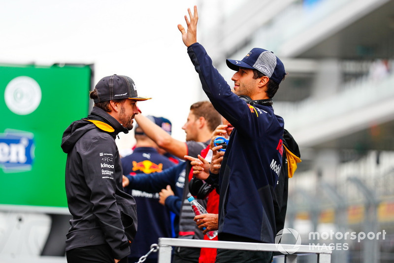 Daniel Ricciardo, del Red Bull Racing, saluda a la multitud en el desfile de pilotos con Fernando Alonso, McLaren