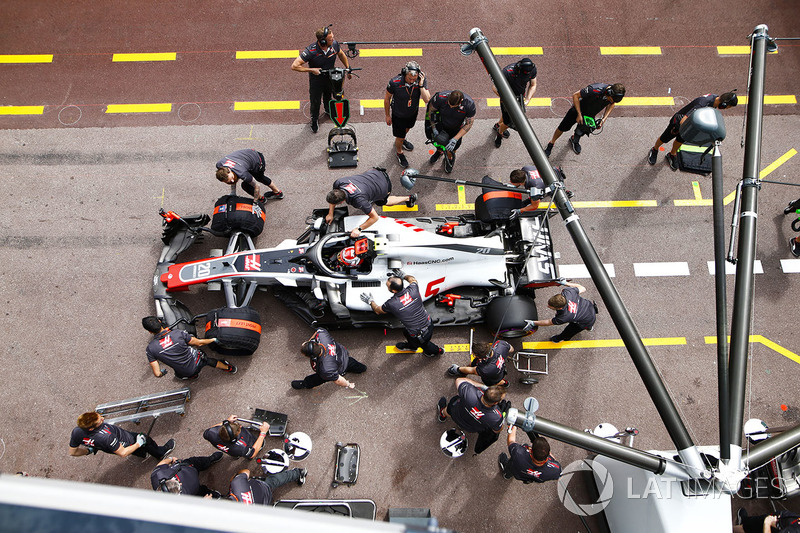 Kevin Magnussen, Haas F1 Team VF-18, is serviced by mechanics in the pit lane