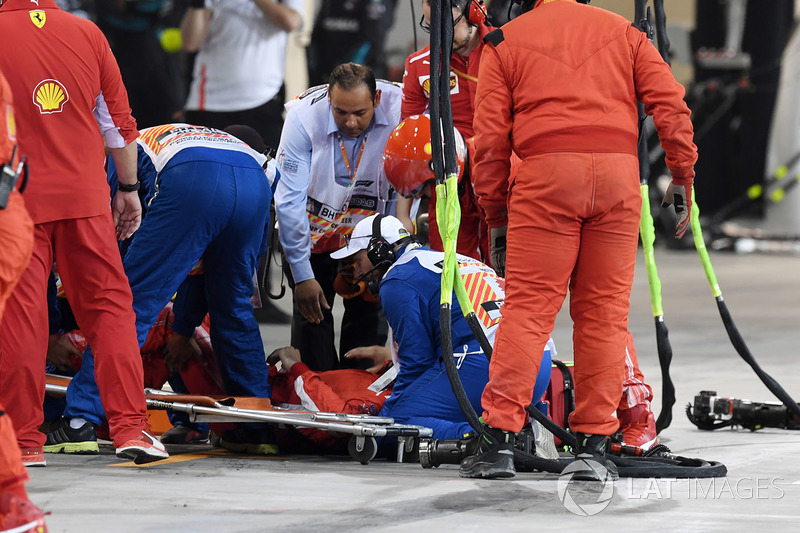 A Ferrari mechanic is tended by medics after being hit by the car of Kimi Raikkonen, Ferrari SF71H during a pit stop