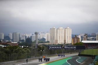 Pierre Gasly, Toro Rosso, et Sergio Perez, Force India, parcourent la piste à pied avec la ville de Sao Paulo au loin