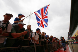 A young Lewis Hamilton, Mercedes AMG F1, supporter in a crowd waves a flag