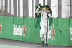 Felipe Massa, Williams, walks back to the garage in tears carrying a Brazilian flag afer crashing