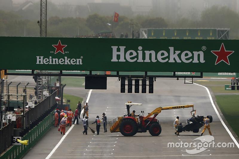 Görevliler Antonio Giovinazzi'nin Sauber C36'sından saçılan parçaları kaldırıyor