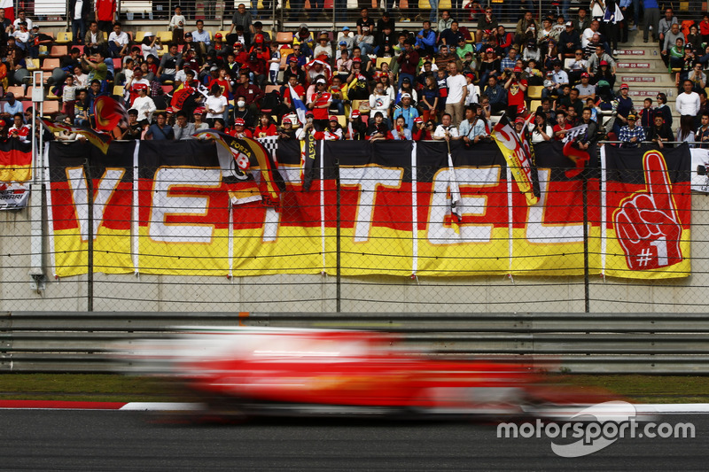 Гонщик Ferrari Себастьян Феттель проносится мимо трибун с болельщиками