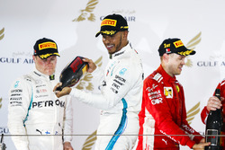 Valtteri Bottas, Mercedes AMG F1, 2nd position, Lewis Hamilton, Mercedes AMG F1, 3rd position, and Sebastian Vettel, Ferrari, 1st position, spray Waard, a non-alcoholic Champagne Rose Water substitute, on the podium