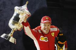 Sebastian Vettel, Ferrari, vainqueur, lève son trophée sur le podium
