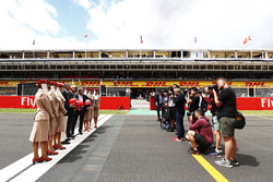 Sean Bratches, Managing Director of Commercial Operations, Formula One Group, Thierry Antinori, Executive Vice President and Chief Commercial Officer, Emirates Airlines, and Chase Carey, Chairman, Formula One, stand opposite photographers with flight attendants