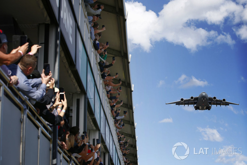 A Royal Australian Air Force Boeing C-17A Globemaster III flies over the grid prior to the start