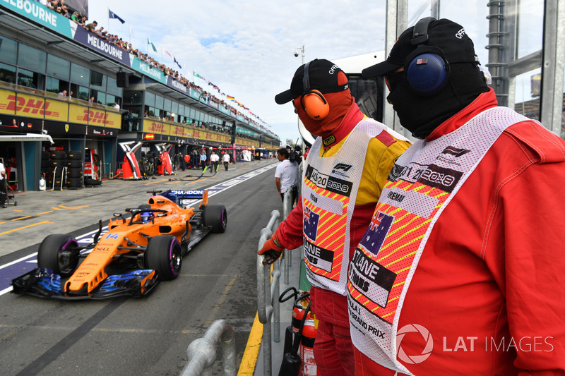 Marshals watch Fernando Alonso, McLaren MCL33 in pit lane
