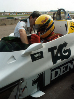 Ayrton Senna, is helped made comfortable by the Williams Team Manager Allan Challis prior to his first run in the Williams FW08C
