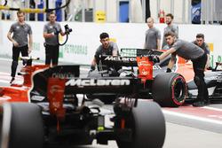 Engineers return Fernando Alonso, McLaren MCL32, to the garage