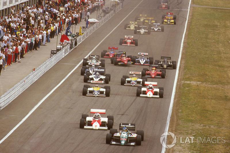 Gerhard Berger, Benetton B186 BMW leads Keke Rosberg, McLaren MP4/2C TAG Porsche, Nelson Piquet, Williams FW11 Honda, Alain Prost, McLaren MP4/2C TAG Porsche, Riccardo Patrese, Brabham BT55 BMW and Nigel Mansell, Williams FW11 Honda at the start, behind Stefan Johansson,Ferrari F186