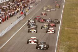 Старт гонки: Герхард Бергер, Benetton B186 BMW, Кеке Росберг, McLaren MP4/2C TAG Porsche, Нельсон Пике, Williams FW11 Honda, Ален Прост, McLaren MP4/2C TAG Porsche, Риккардо Патрезе, Brabham BT55 BMW, и Найджел Мэнселл, Williams FW11 Honda; позади столкновение с участием Стефана Йоханссона,Ferrari F186