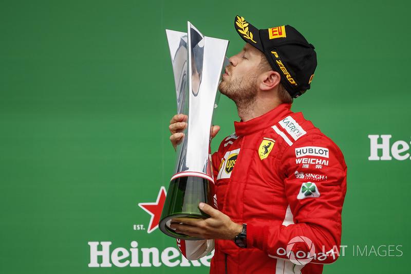 Sebastian Vettel, Ferrari, 1st position, celebrates by kissing his trophy on the podium
