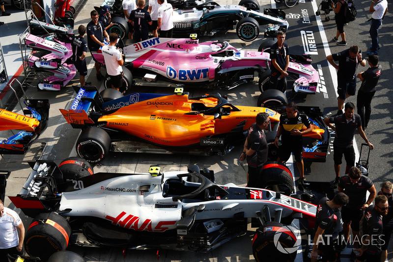 Cars of Kevin Magnussen, Lando Norris, Esteban Ocon, and Lewis Hamilton line up in the pit lane