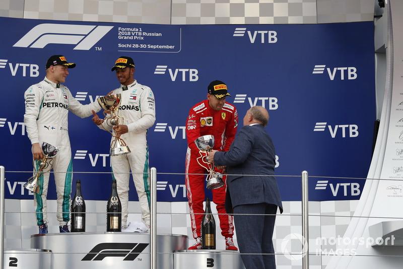 Sebastian Vettel, Ferrari, menerima trofi podium ketiga dari Viktor Kiryanov, President Federasi Otomotif Rusia, di podium