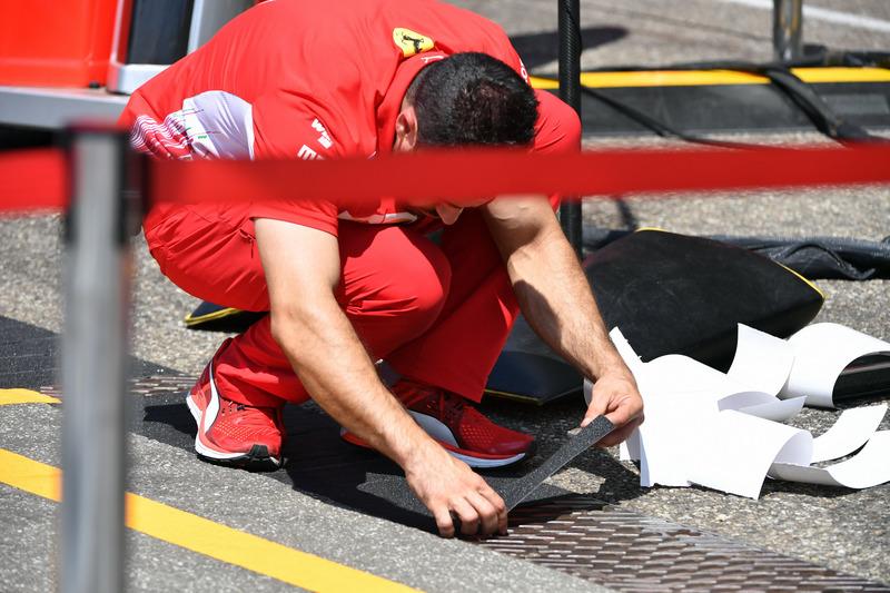 Un mécanicien Ferrari place les marques au sol dans les stands