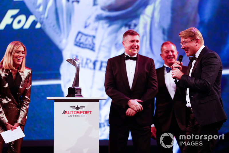 Mika Hakkinen accepts a Gregor Grant Award from Martin Brundle on stage