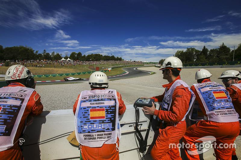 Marshals watch as Felipe Massa, Williams FW40, passes